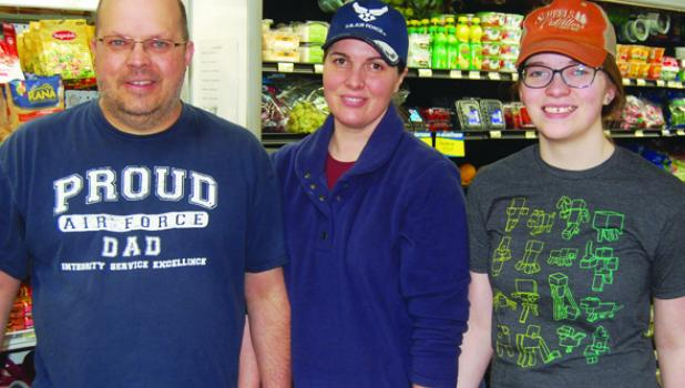 Bill, Kelly and Cora Bolt stand in front of the meat and produce department of their grocery store in Lake Benton.