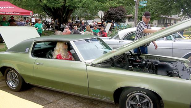 """Steve Kluever of Worthington seated with his """"substitute"""" wife in his 1969 Pontiac."""