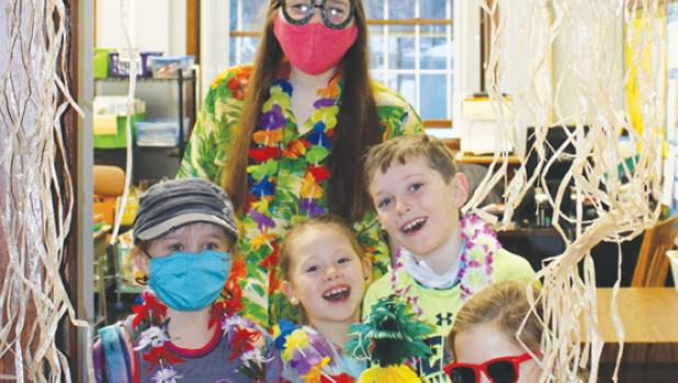 For Hawaiian Day, students played BINGO in the gym. Dressed in themed outfits were: Violet Vlaminck (front), middle row, left to right: Kaitlyn Gorecki, Brisbyn Traen, Sebastian Bothun, and Miss Evers (back).