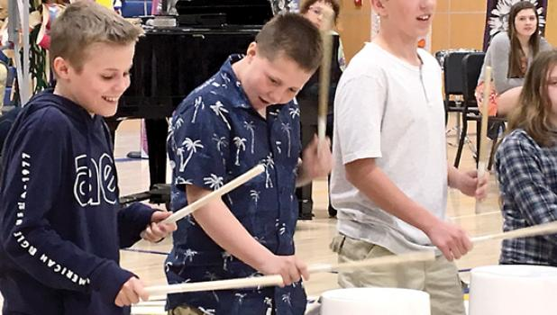 """Enjoying making music on buckets at the 2019 Elementary Spring Concert, """"Sun, Sand, Surf!"""" in Minneota last week were: (left to right) Destin Fier, Kyler Lozinski and Tate Peterson. All are sixth graders."""