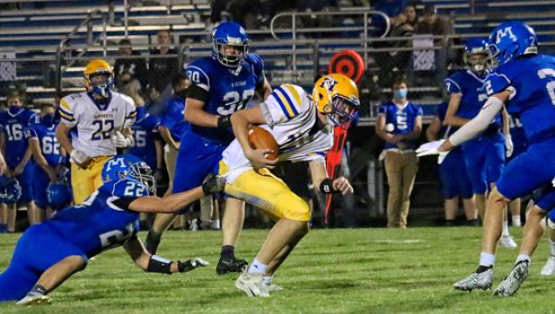 Minneota's AJ Josephson breaks out of the grasp of MACCRAY's Dreyer Homan (22) and scampers 61 yards for a score in the second quarter.