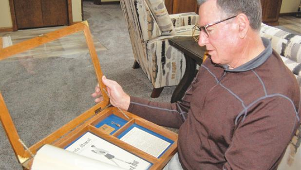 Randy Fox looks over Mascot newspaper clippings that included his father Lawrence boxing for Minneota in the mid-40s.