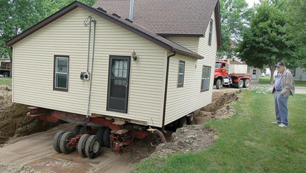 The former Bud Bernardy home was pulled into place at its new location on Jefferson Street as Louie Buysse watched.