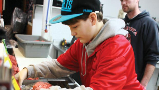 At Brad's, Eli Gruenes  and other students were found wrapping hamburger with Brad Minnehan looking on.