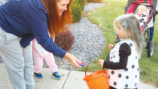Tammy Esping passes out candy to Cruella de Vil, aka Hazel Hammer, 3, on the east side of Minneota during Halloween on Saturday. Hammer is the daughter of Samantha and Michael Hammer.