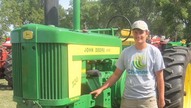 Zach Hennen stands beside the 1957 John Deere 720 he restored recently. Hennen displayed the tractor during Harvest Festival on Saturday in Porter.