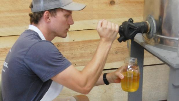 Charlie Pesch fills a quart jar with pure honey from a holding tank.