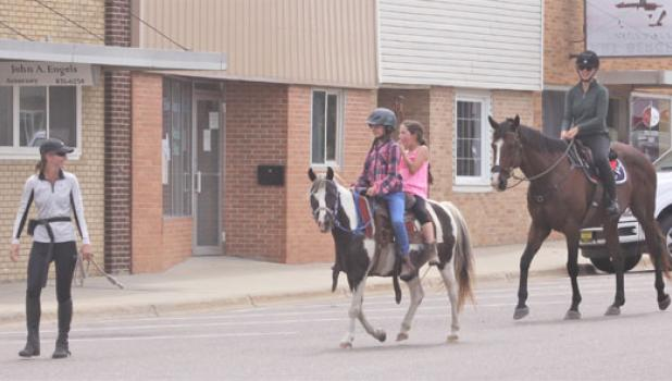 Krystal Howard, left, leads Half Pint with riders Charlotte Brusvig (front), 10, and Savanaah Brunsvig, 8, down main street of Minneota following the Silver Spurs event on Saturday. Following behing on Bentley is Kimberly Cochrane. Howard and Cochraner are trainers. The four girls rode from the Silver Spurs Saddle Club to get some ice cream on a hot day.