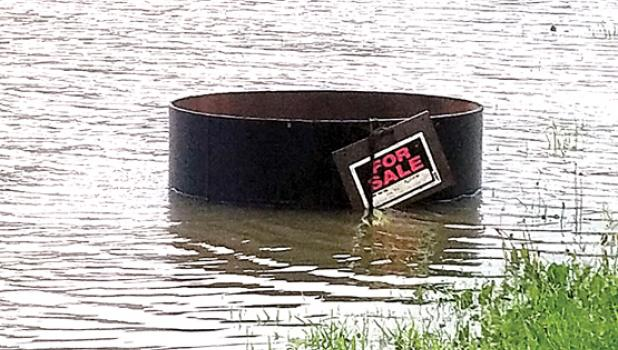 "The heavy downpour on Friday delivered water to this barrel with the ""for sale"" sign — as if to indicate this was a bucket of water for sale."