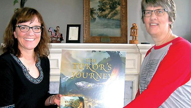 """Jeannine Kellogg presenting the fiction book she wrote to both the Minneota Public Library and to the St. Edward's School. She is shown presenting her book """"Tukor's Journey"""" to Jan Bot of St. Edward's School."""