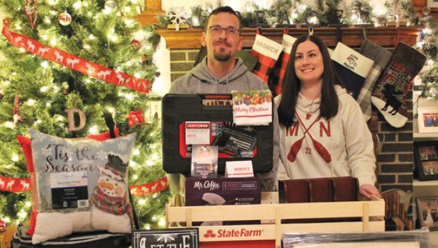 """Austin and Shannon Dritz pose in their home south of Taunton with some of the many prizes they received for winning the Mascot """"Battle of the Bulbs"""" Christmas Lighting Contest this year. There were 29 entries to this year's contest."""