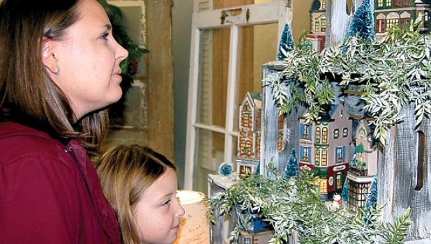 Tegan Gillund and her daughter Sophie admired the large display of Dickens houses at the B Lenore store during the North Pole Extravaganza last Saturday.