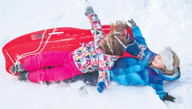 Here, Eva Skorczewski and her sister, Lydia, enjoy sledding downhill on their toboggan outside of Minneota recently. Partway down the hill, though, the siblings had a slight mishap and wiped out.