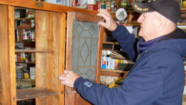 Markell works on putting in one of the glass doors on the Hoosier cabinet he is currently working on.