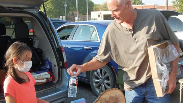 Emily Lasnetski of Ivanhoe accepts a complimentary bottle of water from Kevin Anundson during the Farmers Market last Thursday.