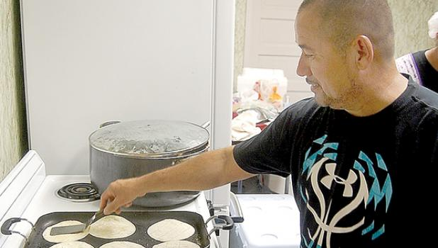 Jamie Rodriguez warms up some taco shells for the Rayo de Luz Church's food stand inside the City Hall building.
