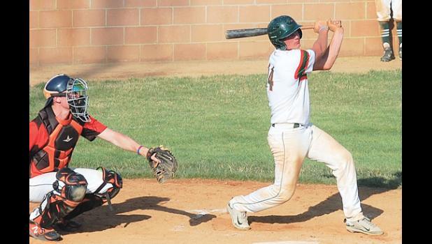 Mudhens catcher Austin DeVlaeminck hits a sacrifice fly to center field in the third inning against Dawson on Saturday in Madison. The Dawson catcher is Braden Thompson.