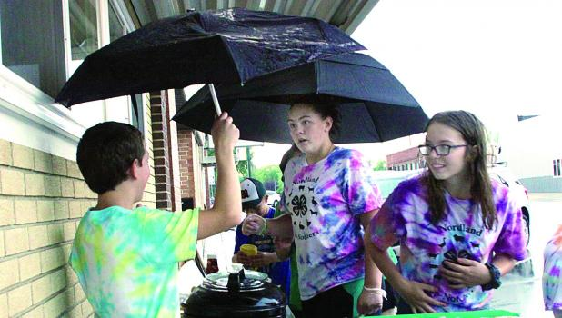 Nordland Top Notchers held their outdoor food sale despite the weather. They served up a hamburger special and also waited on merchants in the community. And they worked around the rain.
