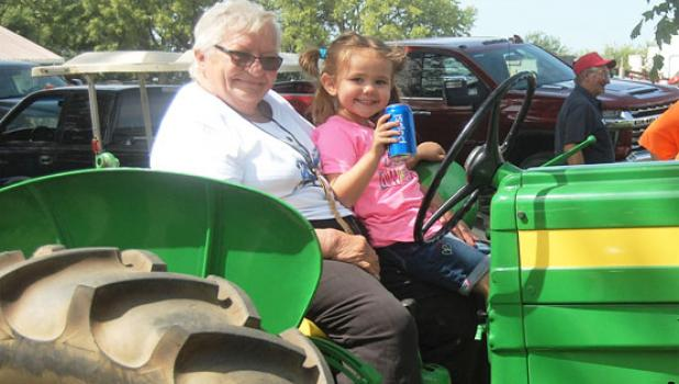 inda Hennen, left, and her granddaughter, Luna Olson, 4, enjoy the Tractor Show and Farm Equipment Demonstrations Saturday during a scaled-down version of Harvest Festival on Saturday in Porter.