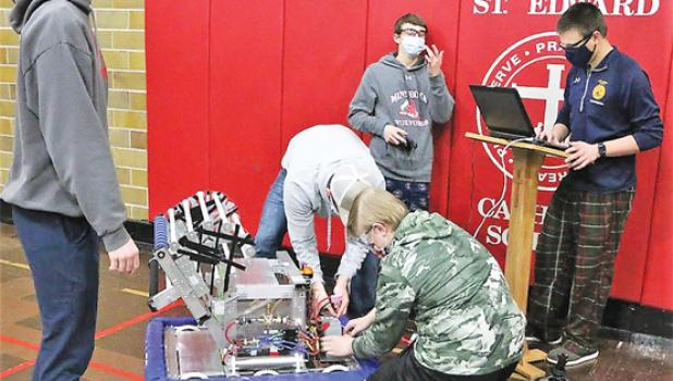 Some members of the Minneota Robotics test out the robot they built. Left to right, Caleb Sterzinger, Carter Schuelke, Joe Voit (kneeling) and Logan Schuelke.