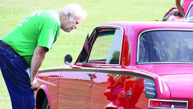 Royal Hettling, who has refurbished his own cars, looked over one of the vehicles at Monday's shows.