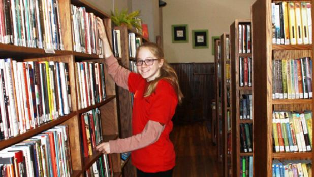 At the Minneota Public Library, student Sarah Gruenes helped dust off shelves, organize books and put books away.
