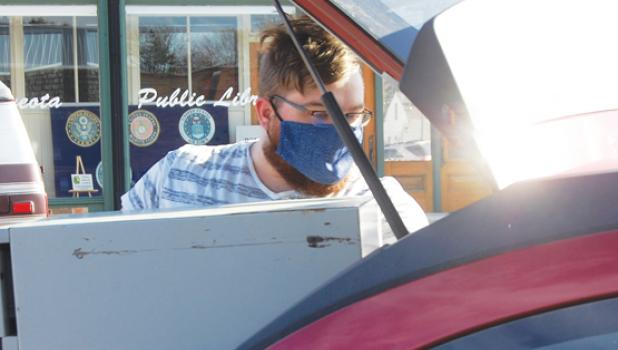 Logan Johnson of Taunton loads  large cabinet into his vehicle after being the winning bidder.