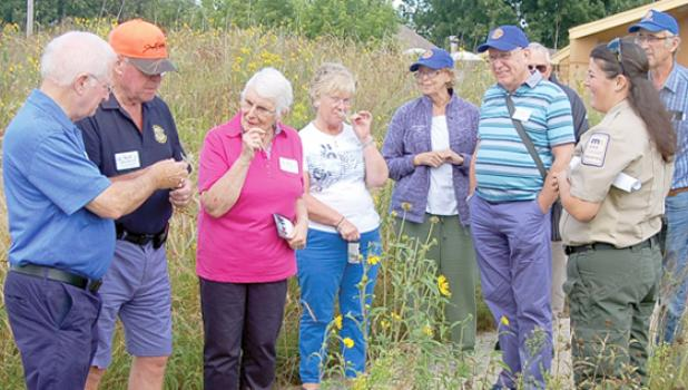 Upper Sioux Agency State Park Assistant Manager Emily Albin gave a tour of the native prairie grasses and flowers of the park. On the right is Rotary host Rick Bot.