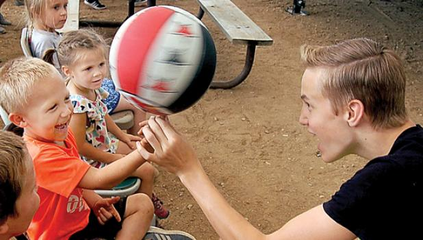 Zack Crevier assists a young audience member in spinning a basketball on his finger.