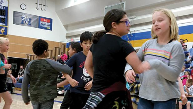They got into it with dance movements or swinging together with a partner. They are: Ruth Monzon and Clare Swedzinski in the Fourth Grade.