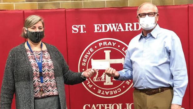 """John Drown, right, founder of the Legacy Foundation of Marshall, presented St. Edward School Principal, Jaci Garvey, left, with a $1,000 donation to St. Edward School """"to help with COVID-related expenses"""" on Wednesday, Oct. 7."""
