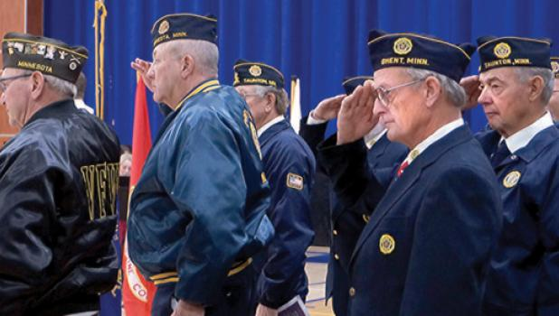 The Minneota Veteran's Day Program held at Minneota High School included a salute by veterans  John DeSmet, Harold DeSmet, Terry Schreiber, with fellow local veterans behind them.