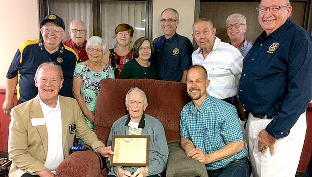 Rotarians gathered around Virgil Ufkin as he got his award from Rotary District Governor Steve Harrington.