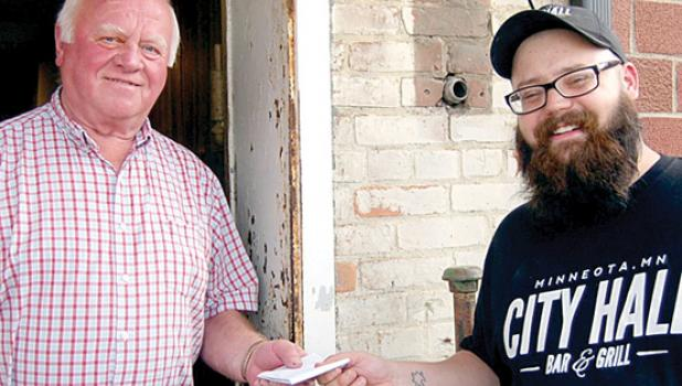 Dave Storlien, left, received $100 gift card from City Hall Bar & Grill Manager Jordan Dressen as the winner of a drawing among those that dined at the business during the week.