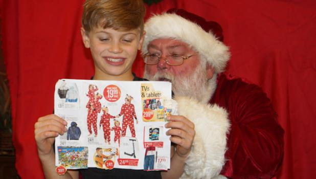 """Santa Claus looked over a brochure of Christmas items with Eli Faris (middle right). It was Eli's """"Wish List."""""""