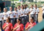 The Minneota girls fastpitch softball team (back) and the St. James team (front), stood in line in honor of the national anthem played before St. James won this playoff game.