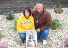 Julie and Donnie III pose with a photo of their son Donnie IV in the memorial garden they are constructing for their son.