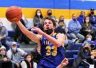 Minneota's AJ Josephson (33) drives past a Canby defender to score two of his 14 points in a Camden Conference game Monday night in Minneota.