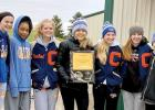 Holding the trophy they captured at the Camden Conference meet at Renville last week were: (left to right) Grace Drietz, Nohemi Diaz, Rachel Wollum, Faith Traen, McKenzie Ruether, Braelyn  Merritt and Claire Stoks.