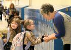 Back to School. Teacher Karen Dalager helped welcome the kids back to the renovated elementary school. Greeting her was Aubrey Stefansen, who was brought to school by her mother Brandi Stefansen. Her cousin Angelica Towne had her attention caught by something else going on.