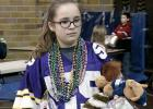 Kylie Callens of the St. Edward School carried off some of her winnings from the Mardi Gras Friday. It was part of the National Education Week festivities at the local Catholic School.
