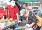 Judy Hagen, right, checks out the fresh vegetables being sold by Brian Pitzl of rural Minneota during the first week of the Farmers Market this past Thursday night at the west end of Veterans Park.
