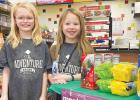 Addyson Pohlen, left, and Brisbyn Traen of Minneota Girl Scouts Troop 37814 remove their facial masks to pose for a photo next to their cookie stand at the C-Store. The girls sold over 60 boxes on Saturday. They will next be selling cookies on Saturday, Feb. 27 from 9 a.m. to noon at the Hy-Vee store in Marshall.