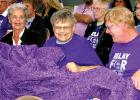 Jimmy Wohnoutka, center, is all smiles after having the Relay for Life quilt given to him by his brother-in-law Dale Karolczak. Seated with Jim is his sister Betty Dubert, left, and brother-in-law Dean Peterson of Marshall.