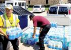 Josue Palacios, left, and Juan Perez unload cases of water at the church in Humble, TX.
