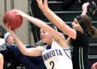 Minneota's Morgan Kockelman grabbed a rebound in front of her Pipestone defender.