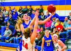 Minneota's Morgan Hennen tried to shovel the ball to the basket against Lac qui Parle Valley defender Katlyn Gades as Haley Wollschlager of the Eagles looked on.