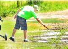Bryan Francis retrieved his ball from a mud hole left on the Countryside Golf Course.