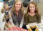 Lori Crowley, left, and Nikki Traen have put their craft talents to work with Pretty Unique and Happy Crafter businesses, respectively. They are shown here at their vendor booth during the North Pole Extravaganza.