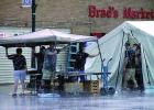 Raindrops fell on the Brad's Market tent as workers held down the awning during the rain storm.